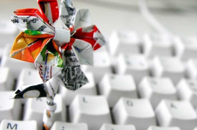Eine Tastatur mit einer aus Papier gefalteten Blume.